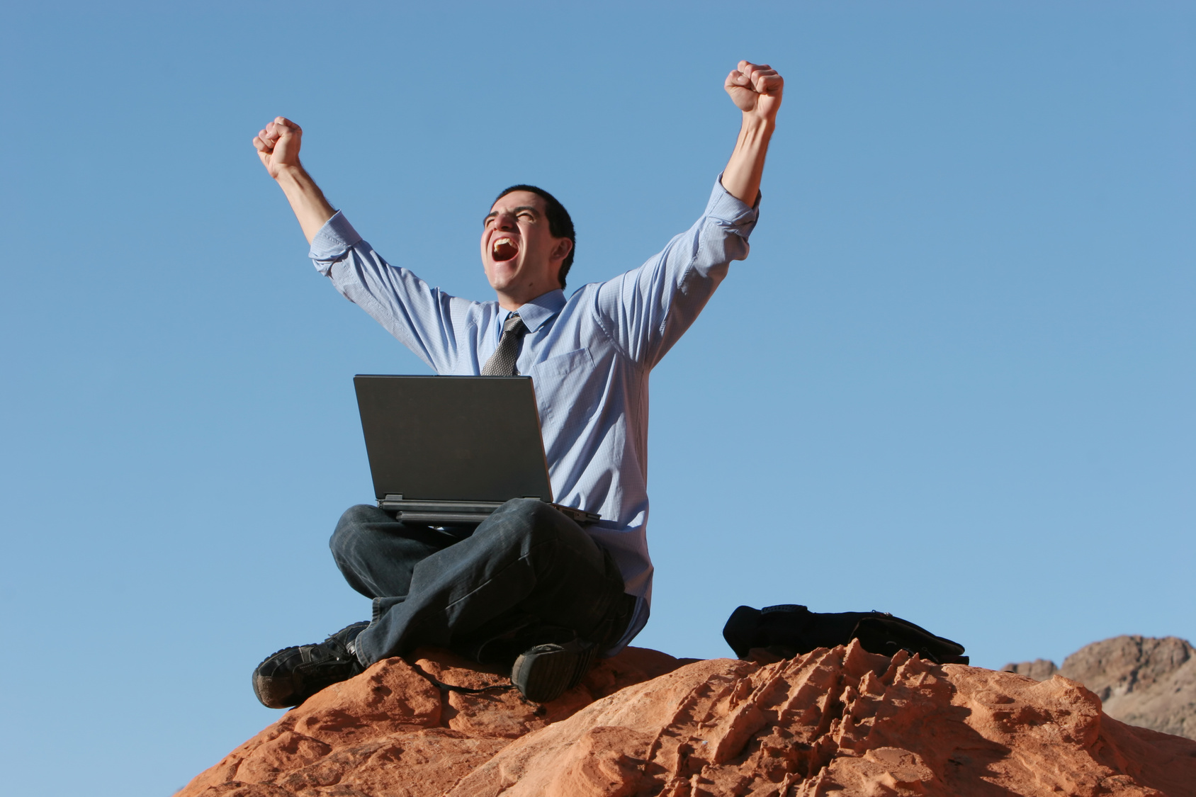 Happy businessman working on laptop on top of the hill