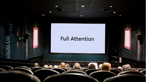 audience in auditorium looking on a screen with title full attention